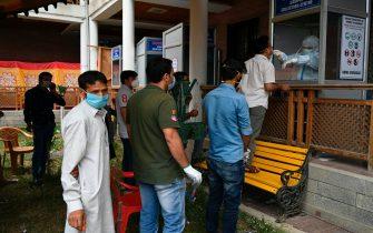 People wait in queue as a health worker (R) takes nasal swab samples to test for the COVID-19 coronavirus at a testing centre in Srinagar on July 21, 2020. - India on July 17 hit a million coronavirus cases, the third-highest total in the world, with no sign yet of the infection curve flattening as new cases emerge in rural areas. More than 25,000 people have died nationally. (Photo by TAUSEEF MUSTAFA / AFP) (Photo by TAUSEEF MUSTAFA/AFP via Getty Images)