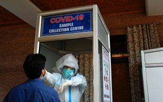 A health worker takes a nasal swab sample from a man to test for the COVID-19 coronavirus at a testing centre in Srinagar on July 21, 2020. - India on July 17 hit a million coronavirus cases, the third-highest total in the world, with no sign yet of the infection curve flattening as new cases emerge in rural areas. More than 25,000 people have died nationally. (Photo by TAUSEEF MUSTAFA / AFP) (Photo by TAUSEEF MUSTAFA/AFP via Getty Images)