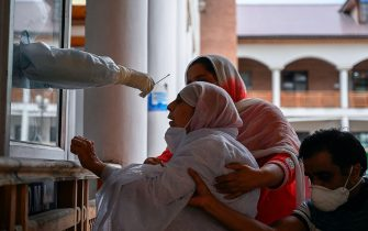 Relatives hold an elderly woman (C) as a health worker takes a nasal swab sample to test for the COVID-19 coronavirus at a testing centre in Srinagar on July 21, 2020. - India on July 17 hit a million coronavirus cases, the third-highest total in the world, with no sign yet of the infection curve flattening as new cases emerge in rural areas. More than 25,000 people have died nationally. (Photo by TAUSEEF MUSTAFA / AFP) (Photo by TAUSEEF MUSTAFA/AFP via Getty Images)