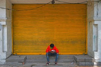 A man sits in front of a closed retail shop in a street during a lockdown to contain the surge of COVID-19 coronavirus cases, in Bangalore on July 20, 2020. - India on July 17 hit a million coronavirus cases, the third-highest total in the world, with no sign yet of the infection curve flattening as new cases emerge in rural areas. More than 25,000 people have died nationally. (Photo by Manjunath Kiran / AFP) (Photo by MANJUNATH KIRAN/AFP via Getty Images)