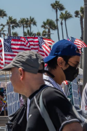 People cross the street in Huntington Beach, California, on July 19, 2020 amid the coronavirus pandemic. - The United States today, June 19, 2020, recorded 63,872 new coronavirus cases in the previous 24 hours, Johns Hopkins University reported in its real-time tally. Orange County saw a lot of protests against wearing masks.  Few people encountered along city streets on a recent afternoon wore masks. (Photo by Apu GOMES / AFP) (Photo by APU GOMES/AFP via Getty Images)