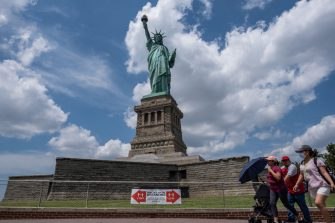 NEW YORK, NY - JULY 20: Visitors walk past the Statue of Liberty as it reopened on Liberty Island on July 20, 2020 in New York City. Liberty Island is partially reopening months after the attraction was shut down due to the coronavirus pandemic. Access to Liberty Island has reopened but the statue itself, the pedestal and museum remain closed. (Photo by Jeenah Moon/Getty Images)