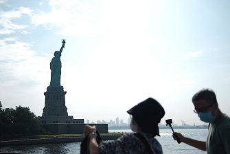 Tourists take pictures of the reopened Liberty Island with the Statue of Liberty in front of the skyline of Lower Manhattan on July 20, 2020 in New York City. - Just a few tourists visited the reopened monument as New York City moves into Phase 4 of the Coronavirus lockdown. (Photo by Johannes EISELE / AFP) (Photo by JOHANNES EISELE/AFP via Getty Images)