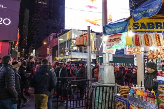 NEW YORK, NY - JANUARY 01: A hot dog stand vendor looks on as people walk through in Times Square on January 1, 2020, in New York City. Times Square is a major commercial intersection, tourist destination, entertainment center, and neighborhood in the Midtown Manhattan section of New York City, at the junction of Broadway and Seventh Avenue.  (Photo by Paul Rovere/Getty Images)