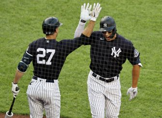 NEW YORK, NEW YORK - JULY 19:  Giancarlo Stanton #27 of the New York Yankees congratulates teammate Aaron Judge #99 after Judge hit a solo home run in the first inning against the New York Mets during Summer Camp play at Yankee Stadium on July 19, 2020 in the Bronx borough of New York City. (Photo by Elsa/Getty Images)