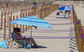 SANXENXO, SPAIN - JULY 11: Wooden poles separate and divide into squares the sandbank on July 11, 2020 in Sanxenxo, Galicia, Spain. The Sanxenxo town council has adapted Silgar beach, in the Rias Baixas region, to protect bathers and tourists from the Covid-19 pandemic. (Photo by Xurxo Lobato/Getty Images)