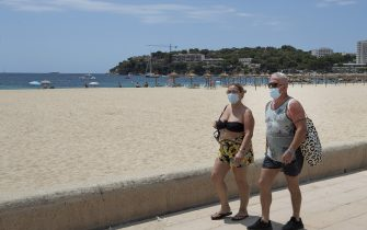 Tourists walk at Magaluf beach, Calvia, in Spain's Balearic island of Majorca on July 16, 2020. - Regional authorities on Spain's Balearic island of Majorca ordered the immediate closure of bars on three streets popular with hard drinking tourists to limit the potential for coronavirus outbreaks. (Photo by JAIME REINA / AFP) (Photo by JAIME REINA/AFP via Getty Images)