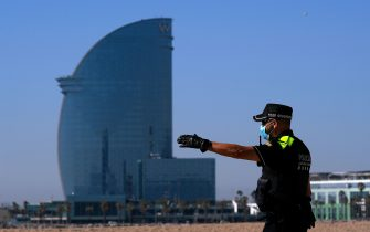 A Spanish policeman asks people that were sunbathing to leave the Barceloneta beach in Barcelona on May 20, 2020 during the hours allowed by the government to exercise, amid the national lockdown to prevent the spread of the COVID-19 disease. - Barcelona opened its beaches and parks for walks, in a slight relaxation of lockdown measures. (Photo by LLUIS GENE / AFP) (Photo by LLUIS GENE/AFP via Getty Images)