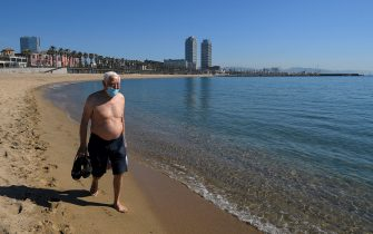 A man wearing a face mask walks at Barceloneta beach in Barcelona on May 20, 2020 during the hours reserved for the elderly, amid the national lockdown to prevent the spread of the COVID-19 disease. - Barcelona opened its beaches and parks for walks, in a slight relaxation of lockdown measures. (Photo by LLUIS GENE / AFP) (Photo by LLUIS GENE/AFP via Getty Images)