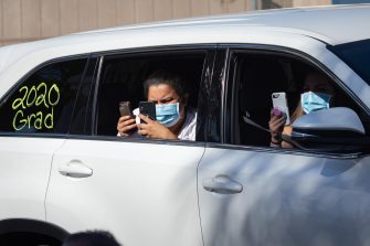 epa08557583 Family members of a graduate take pictures while wearing masks at a graduation ceremony at the California High School amid the coronavirus pandemic in Whittier, California, USA, 20 July 2020. Friends and family members were required to stay in their cars as the students were handed their diplomas by school staff who were social distancing and wearing masks, due to the coronavirus pandemic.  EPA/CHRISTIAN MONTERROSA
