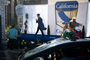 epa08557581 Family members take photos of a graduate after he receives his diploma from the California High School amid the coronavirus pandemic in Whittier, California, USA, 20 July 2020. Friends and family members were required to stay in their cars as the students were handed their diplomas by school staff who were social distancing and wearing masks, due to the coronavirus pandemic.  EPA/CHRISTIAN MONTERROSA