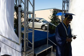 epa08557592 A graduate walks off the stage after receiving his diploma from the California High School amid the coronavirus pandemic in Whittier, California, USA, 20 July 2020. Friends and family members were required to stay in their cars as the students were handed their diplomas by school staff who were social distancing and wearing masks, due to the coronavirus pandemic.  EPA/CHRISTIAN MONTERROSA