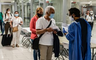 A health worker checks the medical documents of mask-clad travellers arriving at Cyprus' Larnaca International Airport on June 9, 2020, before being screened for COVID-19 coronavirus symptoms on their way to passport control. - Cyprus opened back up for international tourism on June 9, with airports welcoming visitors after an almost three-month shutdown due to the novel coronavirus pandemic, with a bold plan to cover health care costs for visitors. (Photo by Iakovos Hatzistavrou / AFP) (Photo by IAKOVOS HATZISTAVROU/AFP via Getty Images)