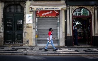 A man wearing a face mask passes by a closed souvenir shop in downtown Lisbon on June 23, 2020. - Portugal's Prime Minister Antonio Costa said on June 22, 2020 that some coronavirus restrictions would be reimposed in the capital Lisbon to help control outbreaks from the pandemic. According to official data compiled by local media, between May 21 and June 21, Portugal recorded 9,221 new cases of COVID-19 with most cases detected in the Lisbon and Tagus Valley regions. (Photo by PATRICIA DE MELO MOREIRA / AFP) (Photo by PATRICIA DE MELO MOREIRA/AFP via Getty Images)