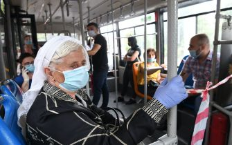 Passengers wear protective face masks as they ride a bus in Tirana on July 6, 2020 as public transport resumes after a closure of some 4 months due to the novel coronavirus, COVID-19 pandemic. (Photo by Gent SHKULLAKU / AFP) (Photo by GENT SHKULLAKU/AFP via Getty Images)