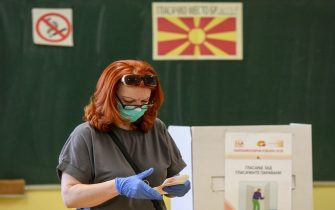 "A woman wearing a face mask and protective gloves cast her vote in a polling station during the general election in Skopje on July 15, 2020. - North Macedonia went to the polls on July 15, 2020 in a tight parliamentary election whose winners will face a surging coronavirus outbreak and the start of talks to join the European Union. It is the first parliamentary election since the Balkan country added ""North"" to its name early last year, ending a decades-old dispute with Greece. (Photo by Robert ATANASOVSKI / AFP) (Photo by ROBERT ATANASOVSKI/AFP via Getty Images)"