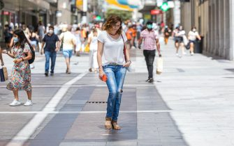 MADRID, SPAIN - JULY 20: A woman walks on Preciados Street without a mask on July 2, 2020 in Madrid, Spain. Together with the Canary Islands, the Community of Madrid is the only one where it is not yet mandatory to wear a mask. (Photo by David Benito/Getty Images)
