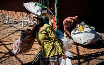 A woman walks while carrying a food parcel at a food distribution by Meals on Wheels in Brapkan, Ekurhuleni, on July 6, 2020. - As Gauteng province's COVID-19 coronavirus infection rate soared to 63 404 positive cases on Sunday 5 July, Meals on Wheels South Africa continues preparing and delivering meals and food parcels to those in need in urban and rural communities. (Photo by Michele Spatari / AFP) (Photo by MICHELE SPATARI/AFP via Getty Images)