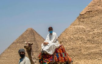 A mask-clad camel guide rides a camel near the (L to R) Great Pyramid of Khufu (Cheops) and Pyramid of Khafre (Chephren) at the Giza Pyramids necropolis on the southwestern outskirts of the Egyptian capital Cairo on July 1, 2020 as the archaeological site reopens while the country eases restrictions put in place due to the COVID-19 coronavirus pandemic. - A spree of openings in Egypt comes after the country officially ended a three-month nighttime curfew a few days earlier. Cafes and shops have re-opened but public beaches and parks remain closed as part of measures to curb the spread of the novel coronavirus. Egypt has recorded more than 65,000 COVID-19 cases including over 2,700 deaths. (Photo by Khaled DESOUKI / AFP) (Photo by KHALED DESOUKI/AFP via Getty Images)
