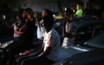 """Spectators watch sitting on the hood of their parked cars a stage play called Pidgin English """"Grip am"""" (Hold it) at a drive-in theatre in Abuja on May 30, 2020 as lockdown restrictions to contain the outbreak of COVID-19 coronavirus are relaxed in the country. (Photo by Kola Sulaimon / AFP) (Photo by KOLA SULAIMON/AFP via Getty Images)"""