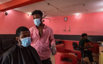 Kofi (C), a barber, resumes work after the partial lockdown in parts of Ghana to halt the spread of the COVID-19 coronavirus was lifted in Accra, Ghana on April 20, 2020. - The streets of Accra buzzed with life following President Nana Akufo-Addo's announcement of the end to a three-week restriction on movement around the capital and second region Kumasi. (Photo by Nipah Dennis / AFP) (Photo by NIPAH DENNIS/AFP via Getty Images)