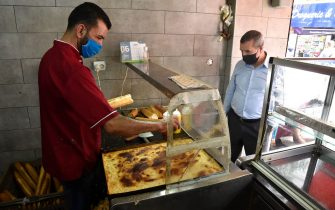 An Algerian man buys a sandwich at a shop in the capital Algiers on June 7, 2020, after authorities eased some restrictions put in place in a bid to fight the spread of the novel coronavirus. (Photo by RYAD KRAMDI / AFP) (Photo by RYAD KRAMDI/AFP via Getty Images)