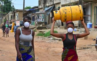 A woman carrying a gas bottle on her head while wearing a mask as a preventive measure against the spread of the COVID-19 Coronavirusis walks through the Abobo suburbs of Abidjan on March 25, 2020. - A state of emergency, a curfew and a gradual containment of populations to fight the COVID-19 Coronavirus were declared on March 23, 2020 in Ivory Coast by President Alassane Ouattara, in a televised address to the nation. (Photo by ISSOUF SANOGO / AFP) (Photo by ISSOUF SANOGO/AFP via Getty Images)