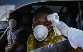 TOPSHOT - A staff member of the Ministry of Health measures the temperature of drivers and passengers during the testing of the COVID-19 Coronavirus on the highway in Nakuru, Kenya, on March 31, 2020. - Kenya has so far recorded 50 cases of coronavirus, and one death. (Photo by Suleiman MBATIAH / AFP) (Photo by SULEIMAN MBATIAH/AFP via Getty Images)