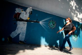 A woman walks in front of a mural depicting a man in protective suit spraying disinfectant on coronavirus with Brazilian President Jair Bolsonaro's face, at the Tijuca neighborhood in Rio de Janeiro, Brazil on July 8, 2020, amid the new coronavirus pandemic. - Brazilian President Jair Bolsonaro has tested positive for the coronavirus after months of downplaying the dangers of the disease. (Photo by MAURO PIMENTEL / AFP) (Photo by MAURO PIMENTEL/AFP via Getty Images)