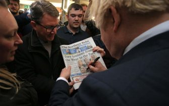 COUNTY DURHAM, ENGLAND - DECEMBER 14: UK Prime Minister Boris Johnson signs a copy of The Northern Echo for a supporter on a visit to meet newly elected Conservative party MP for Sedgefield, Paul Howell at Sedgefield Cricket Club on December 14, 2019 in County Durham, England. Following his Conservative party's general election victory, Prime Minister Boris Johnson called on Britons to put years of bitter divisions over the country's EU membership behind them as he vowed to use his resounding election victory to finally deliver Brexit next month. (Photo by Lindsey Parnaby - WPA Pool/Getty Images)