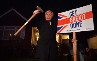 """BENFLEET, UNITED KINGDOM - DECEMBER 11:  Britain's Prime Minister Boris Johnson poses after hammering a """"Get Brexit Done"""" sign into the garden of a supporter during a campaign stop on the final day of campaigning before tomorrow's general election on December 11, 2019 in in Benfleet, United Kingdom. The UK will go to the polls on December 12, the third General Election in less than five years.  (Photo by Ben Stansall - WPA Pool/Getty Images)"""