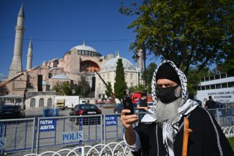 A man wearing a face mask stands in front of Hagia Sophia during the preparations for the Friday prayer in Istanbul, on July 23, 2020. - The first prayers at Hagia Sophia since the Istanbul landmark was reconverted to a mosque will take place on July 23, 2020. Turkey's top court paved the way for the conversion in a decision to revoke the edifice's museum status conferred nearly a century ago. The sixth-century building had been open to all visitors, regardless of their faith, since its inauguration as a museum in 1935. (Photo by Ozan KOSE / AFP) (Photo by OZAN KOSE/AFP via Getty Images)