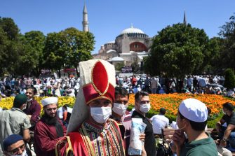 A man wearing a traditional Ottoman costume arrives with others on July 24, 2020 outside Hagia Sophia in Istanbul to attend the Friday prayer, the first muslim prayer held at the landmark since it was reconverted to a mosque despite international condemnation. - A top Turkish court revoked the sixth-century monument's status as a museum on July 10 and Turkish President then ordered the building to reopen for Muslim worship. The UNESCO World Heritage site in historic Istanbul was first built as a cathedral in the Christian Byzantine Empire but was converted into a mosque after the Ottoman conquest of Constantinople in 1453. (Photo by OZAN KOSE / AFP) (Photo by OZAN KOSE/AFP via Getty Images)