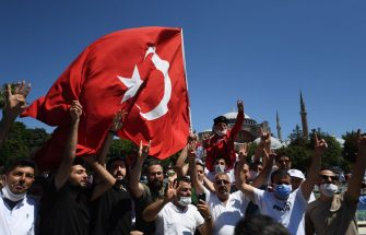 Men waves a Turkish national flag and flash the four finger Rabia sign as people gather on July 24, 2020 outside Hagia Sophia in Istanbul to attend the Friday prayer, the first muslim prayer held at the landmark since it was reconverted to a mosque despite international condemnation. - A top Turkish court revoked the sixth-century monument's status as a museum on July 10 and Turkish President then ordered the building to reopen for Muslim worship. The UNESCO World Heritage site in historic Istanbul was first built as a cathedral in the Christian Byzantine Empire but was converted into a mosque after the Ottoman conquest of Constantinople in 1453. (Photo by OZAN KOSE / AFP) (Photo by OZAN KOSE/AFP via Getty Images)