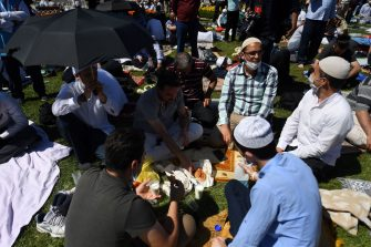 Men eat as they wait on July 24, 2020 outside Hagia Sophia in Istanbul to attend the Friday prayer, the first muslim prayer held at the landmark since it was reconverted to a mosque despite international condemnation. - A top Turkish court revoked the sixth-century monument's status as a museum on July 10 and Turkish President then ordered the building to reopen for Muslim worship. The UNESCO World Heritage site in historic Istanbul was first built as a cathedral in the Christian Byzantine Empire but was converted into a mosque after the Ottoman conquest of Constantinople in 1453. (Photo by OZAN KOSE / AFP) (Photo by OZAN KOSE/AFP via Getty Images)