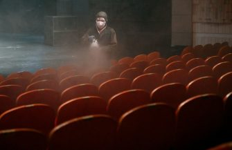 A South Korean worker wearing protective clothes sprays disinfectant in a theatre at Sejong Center in Seoul on July 21, 2020, amid the COVID-19 coronavirus pandemic. (Photo by Jung Yeon-je / AFP) (Photo by JUNG YEON-JE/AFP via Getty Images)