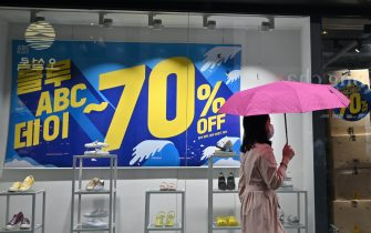 A woman walks past a commercial sign at a shopping district in Seoul on July 23, 2020. - South Korea's economy recorded its worst performance in more than 20 years in the second quarter, the central bank said on July 23, as the coronavirus pandemic hammered its exports. (Photo by Jung Yeon-je / AFP) (Photo by JUNG YEON-JE/AFP via Getty Images)