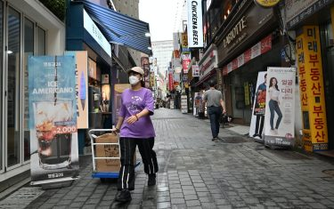 A woman pulls a cart at a shopping district in Seoul on July 23, 2020. - South Korea's economy recorded its worst performance in more than 20 years in the second quarter, the central bank said on July 23, as the coronavirus pandemic hammered its exports. (Photo by Jung Yeon-je / AFP) (Photo by JUNG YEON-JE/AFP via Getty Images)