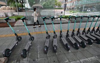 A woman walks past electric kickboards parked on a street in central Seoul on July 23, 2020. - South Korea's economy recorded its worst performance in more than 20 years in the second quarter, the central bank said on July 23, as the coronavirus pandemic hammered its exports. (Photo by Jung Yeon-je / AFP) (Photo by JUNG YEON-JE/AFP via Getty Images)