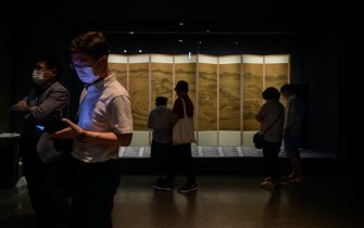 Visitors wearing face masks look at a 'New National Treasures' exhibition at the National Museum of Korea in Seoul on July 23, 2020. - Cultural venues in Seoul have re-opened following a slowdown in COVID-19 coronavirus infections, emerging from lockdown for the second time since the start of the pandemic after an uptick in local cases in late May. As part of virus-related restrictions on visitor numbers, Seoul's National Museum of Korea is operating a reservation system allowing up to 200 visitors into exhibitions in two-hour viewing sessions. (Photo by Ed JONES / AFP) (Photo by ED JONES/AFP via Getty Images)