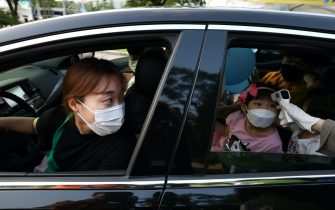 SEOUL, SOUTH KOREA - JULY 17: A mother watches as event staff check her daughter's temperature as they arrive to watch a drive-in concert as South Koreans take measures to protect themselves against the spread of coronavirus (COVID-19) on July 17, 2020 in Seoul, South Korea. South Korea's new daily virus cases came in at around 60 for the second straight day on Friday as the country grapple with rising imported cases and an uptick in local infections. The country added 60 cases today, including 21 local infections, raising the total caseload to 13,672, according to the Korea Centers for Disease Control and Prevention (KCDC). (Photo by Chung Sung-Jun/Getty Images)
