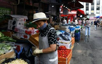 SEOUL, SOUTH KOREA - JULY 21: A street vender wears a mask to prevent the coronavirus at the Namdaemun market on July 21, 2020 in Seoul, South Korea. With the number of daily local cases recently hovering around 20 or below, but imported cases continued to rise by double digit figures. South Korea resumed operations of some museums and libraries in the greater Seoul area starting yeaterday. Health authorities, however, are still vigilant over the spread of the virus in vacation spots over the summer, pointing out that the season will serve as a critical juncture for the nation's anti-virus fight. The country added 45 cases toddy, including 20 local infections, raising the total caseload to 13,816, according to the Korea Centers for Disease Control and Prevention (KCDC). (Photo by Chung Sung-Jun/Getty Images)