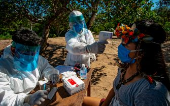 Indigenous nurses from the Special Secretariat for Indigenous Health (Sesai) of the Arapiuns ethnic group and Tapuia ethnic groups perform a rapid COVID-19 test on Marline Jesus Campos from the Arapium tribe on the banks of the lower Tapajos River in the municipality of Santarem in western Para on July 19, 2020. (Photo by TARSO SARRAF / AFP) (Photo by TARSO SARRAF/AFP via Getty Images)
