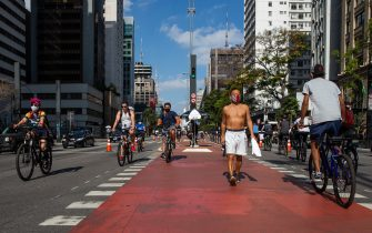 SAO PAULO, BRAZIL - JULY 19: Cyclists ride in Paulista Avenue bicycle lane amidst the coronavirus (COVID-19) pandemic on July 19, 2020 in Sao Paulo, Brazil. Leisure bike lanes in Sao Paulo returned to operation on weekends after almost a year closed. (Photo by Alexandre Schneider/Getty Images)