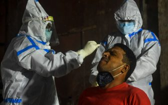 A health worker collects a swab sample from a resident (C) of a containment zone to test for the COVID-19 coronavirus in Kolkata on July 23, 2020. - India last week became the third country after the United States and Brazil to hit one million cases but many experts say that with testing rates low, the true number could be much higher. (Photo by Dibyangshu SARKAR / AFP) (Photo by DIBYANGSHU SARKAR/AFP via Getty Images)