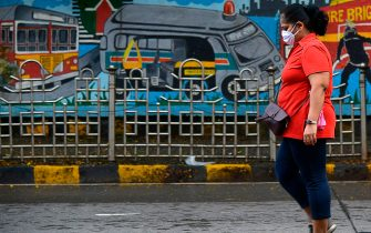 A woman wearing a facemask walks along a sidewalk as the government extended a lockdown to fight against the surge in COVID-19 coronavirus cases, in Mumbai on July 24, 2020. - India last week became the third country after the United States and Brazil to hit one million cases but many experts say that with testing rates low, the true number could be much higher. (Photo by Sujit Jaiswal / AFP) (Photo by SUJIT JAISWAL/AFP via Getty Images)