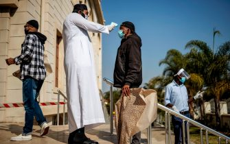 A man carrying a disposable prayer mat and wearing a mask as preventive measure against COVID-19 coronavirus has his temperature checked at the entrance of the Nizamiye Mosque ahead of the Friday prayer in Midrand, Johannesburg, on June 5, 2020 as faith activities have resumed in South Africa since June 1 with the introduction of the level 3 lockdown regulation aimed at curbing the spread of the COVID-19 disease. (Photo by Michele Spatari / AFP) (Photo by MICHELE SPATARI/AFP via Getty Images)