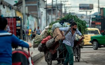 A man pulls a cart in Bogota, on July 23, 2020, amid the new coronavirus pandemic. - The mayor of Bogota, Claudia Lopez, expanded a coronavirus lockdown from Thursday to cover five million residents of the Colombian capital after the government refused to authorize a total shutdown. Bogota is trying to avoid the collapse of its intensive care facilities which have reached 91.5 percent occupancy, according to official figures. (Photo by Juan BARRETO / AFP) (Photo by JUAN BARRETO/AFP via Getty Images)