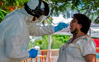 A health worker collects a swab sample from a woman for a COVID-19 test, in Merida, Yucatan state, Mexico, on July 24, 2020, amid the novel coronavirus pandemic. (Photo by HUGO BORGES / AFP) (Photo by HUGO BORGES/AFP via Getty Images)