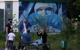 "KRASNOGORSK, RUSSIA - JULY 10: (RUSSIA OUT) A man drinks beer as other people without protective masks have a rest in the square, as graffiti depicting a doctor and sign ""COVID-19"" are seen at the hall of the building, on July 10,2020 in Krasnogorsk, outside of Moscow, Russia. The requirement to wear masks and gloves to combat a spread of the Coronavirus (COVID-19) is still in effect in Moscow. (Photo by Mikhail Svetlov/Getty Images)"